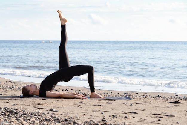 Jonge vrouw in zwarte doen yoga op zand strand bij zonsopgang