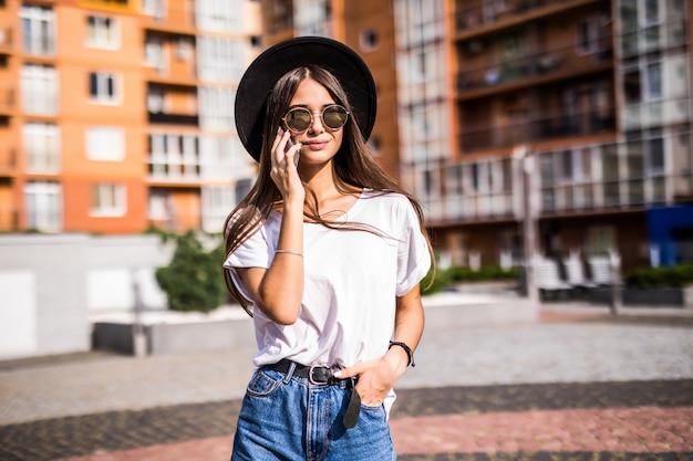Jonge vrouw in zwarte hoed die mobiele telefoon op stadsstraat met behulp van. meisje praten aan de telefoon