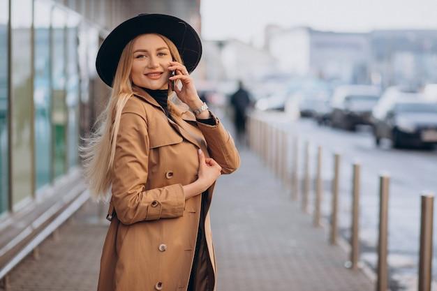 Jonge vrouw in zwarte hoed die telefoon met behulp van