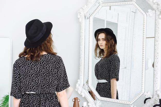 Jonge vrouw in zwarte hoed en jurk kijkt in de spiegel