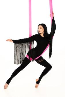 Jonge vrouw in zwarte jumpsuit praktijken antenne inversie antigravity yoga met roze hangmat