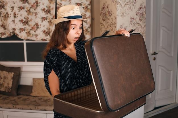 Jonge vrouw in zwarte jurk met een halfopen koffer in haar handen. vintage-stijl.