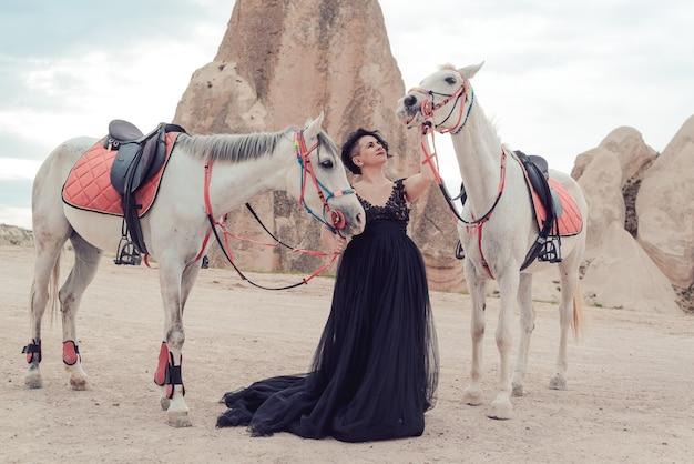 Jonge vrouw in zwarte jurk met haar witte paard buiten