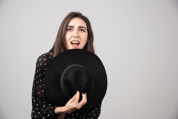 Jonge vrouw in zwarte jurk met hoed tegen haar lichaam.