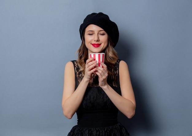 Jonge vrouw in zwarte jurk met kop op grijze muur