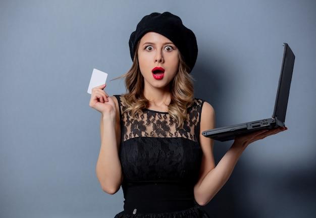 Jonge vrouw in zwarte jurk met laptop en kaart op grijze muur