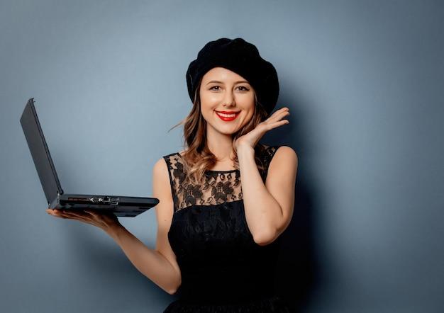 Jonge vrouw in zwarte jurk met laptop op grijze muur