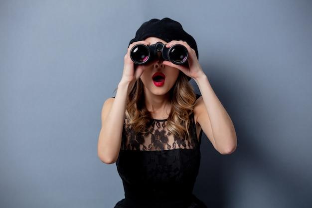 Jonge vrouw in zwarte jurk met verrekijker op grijze muur