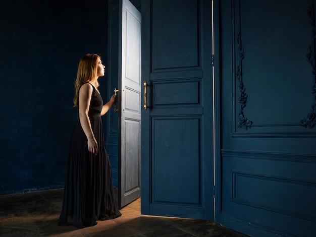 Jonge vrouw in zwarte jurk opent een deur waaruit licht stroomt. de donkere kamer wordt verlicht door mysterieus licht van achter de deur. concept van het ontdekken van geheime kennis en kansen