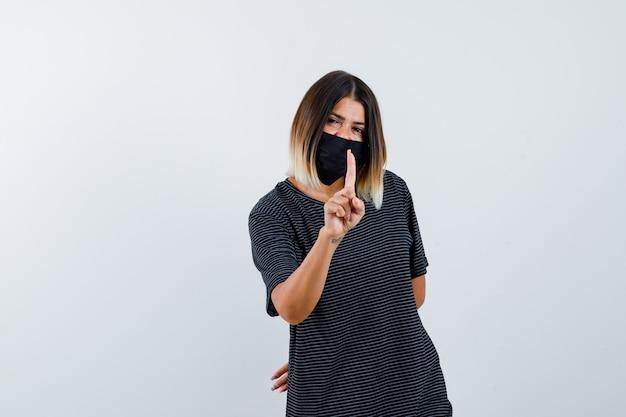 Jonge vrouw in zwarte jurk, zwart masker dat een minuutgebaar vasthoudt, hand achter de taille vasthoudt en er gelukkig uitziet, vooraanzicht.