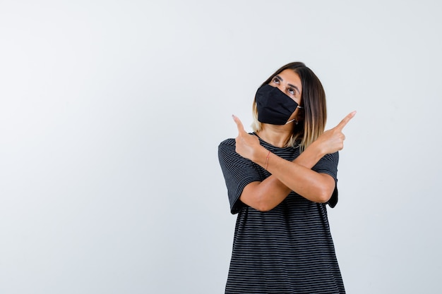 Jonge vrouw in zwarte jurk, zwart masker dat met wijsvinger in tegengestelde richting wijst, naar boven kijkt en peinzend kijkt, vooraanzicht.