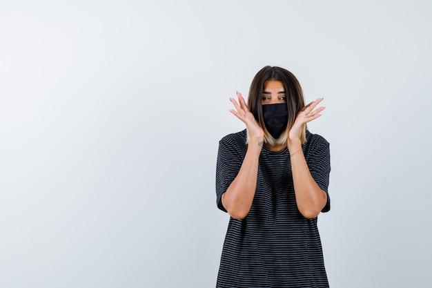Jonge vrouw in zwarte jurk, zwart masker hand in hand in de buurt van wangen en op zoek verrast, vooraanzicht.