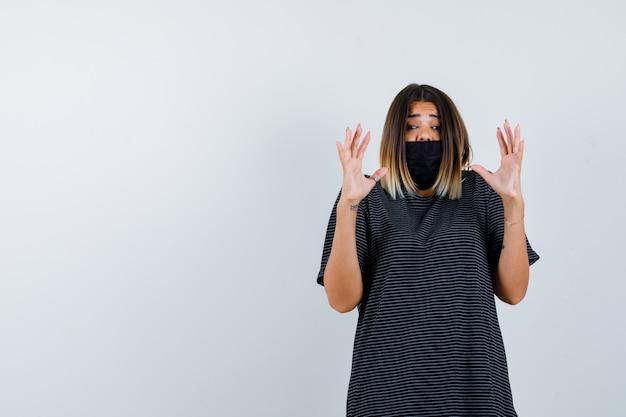 Jonge vrouw in zwarte jurk, zwart masker palmen opheffen in overgave gebaar en bang, vooraanzicht op zoek.