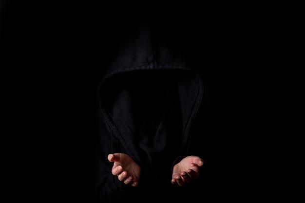 Jonge vrouw in zwarte kap gezicht niet zichtbaar met gestrekte handpalmen tegen donkere zwarte achtergrond.