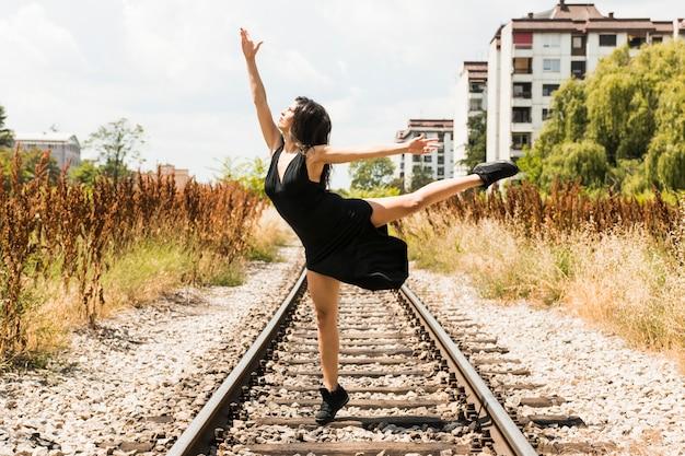 Jonge vrouw in zwarte kleding die bij spoorweg dansen