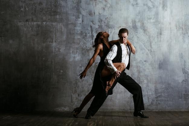 Jonge vrouw in zwarte kleding en man danstango