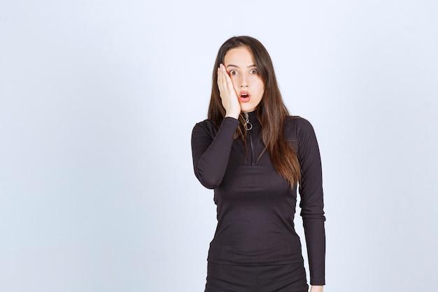 Jonge vrouw in zwarte kleding ziet er doodsbang en bang uit