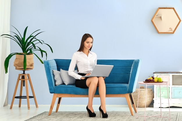 Jonge vrouw in zwarte rok en witte blouse die laptop met behulp van terwijl het zitten op comfortabele bank