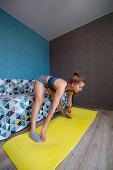 Jonge vrouw in zwarte sportkleding beoefent yoga, staat in de voorste bocht, voert een oefening uit, atletisch meisje oefent thuis of in een yogastudio met grijze muren, lichaam strekken