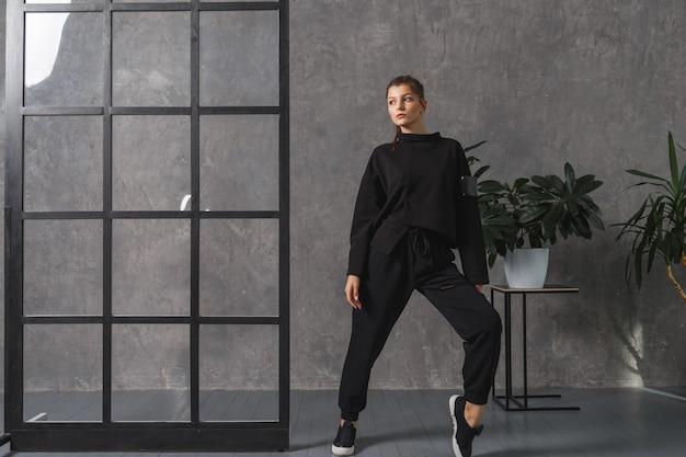 Jonge vrouw in zwarte sportkleding, broek en sweatshirt. concept van modieuze sportoutfit, foto binnenshuis. kopieer ruimte. het concept van sport, gezonde levensstijl, fitness, stretching