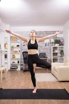 Jonge vrouw in zwarte sportkleding doet yoga boom pose in huis.