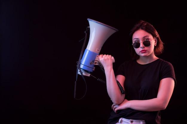 Jonge vrouw in zwarte t-shirt met megafoon