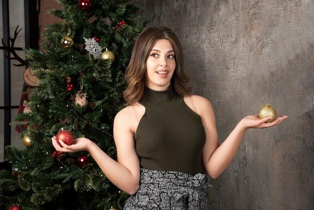 Jonge vrouw in zwarte top met glanzende kerstballen in met kerst versierde kamer