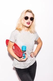 Jonge vrouw in zwarte zonnebril die zich met een skateboard in haar handen bevindt