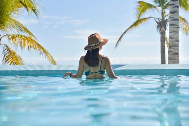Jonge vrouw in zwembad kijkend naar de horizon