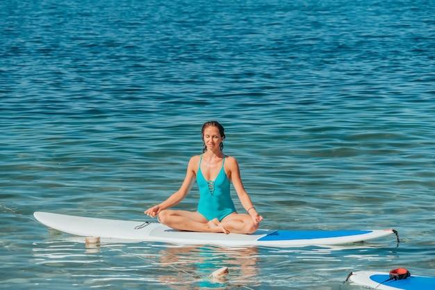 Jonge vrouw in zwembroek doet yoga op sup board meditatieve pose