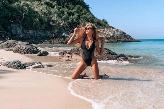 Jonge vrouw in zwembroek poseren op een strand