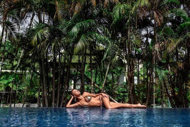 Jonge vrouw in zwembroek poseren op een zwembad