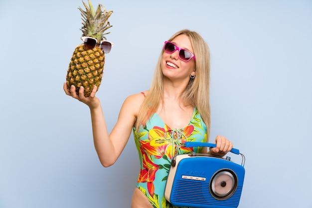 Jonge vrouw in zwempak die een ananas met zonnebril en een radio houden