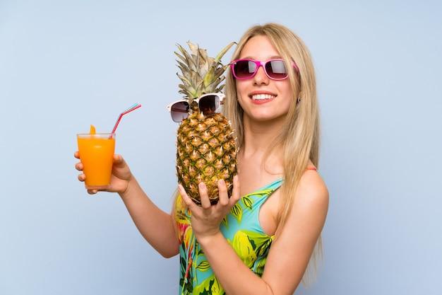 Jonge vrouw in zwempak die een ananas met zonnebril houden