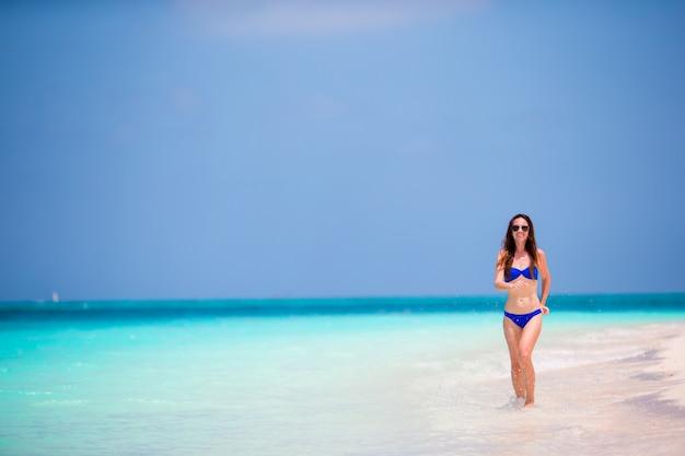 Jonge vrouw in zwempak die en van tijd lopen genieten bij het strand