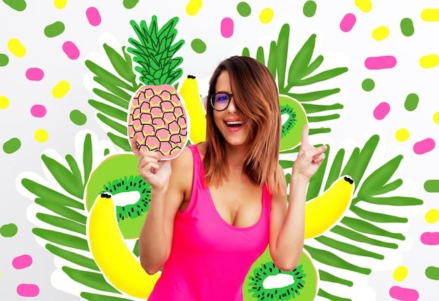 Jonge vrouw in zwempak en oogglazen met ananas