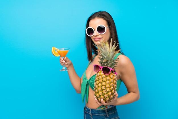 Jonge vrouw in zwempak in de zomervakantie met een cocktail