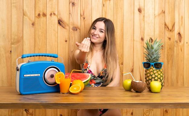 Jonge vrouw in zwempak met veel vruchten die uitnodigen te komen