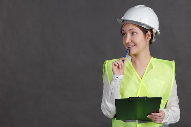Jonge vrouw ingenieur in beschermende helm en vest, glimlachend, knagende pen met tablet in handen.