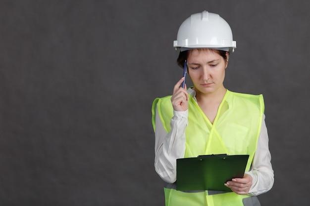 Jonge vrouw ingenieur in beschermende helm en vest met pen en tablet in handen. denkt na over het idee.