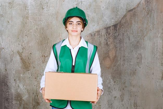 Jonge vrouw ingenieur in groen vest en helm met papieren doos