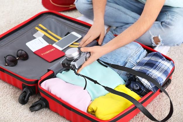 Jonge vrouw inpakken koffer thuis, close-up