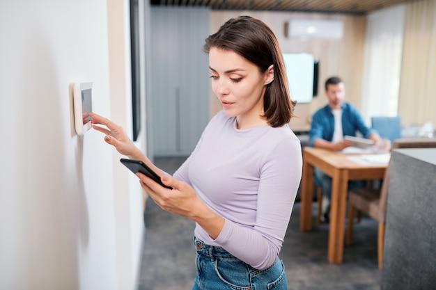 Jonge vrouw installeren nieuw systeem van slimme afstandsbediening in digitale tablet opknoping op de muur van de woonkamer