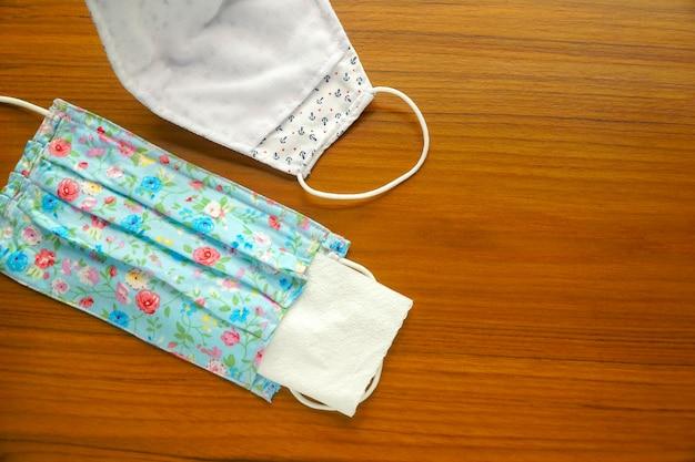 Jonge vrouw invoegen wit papieren zakdoekje in diy-stof katoenen gezichtsmasker. hergebruik. bescherm speeksel, hoest, stof, vervuiling (pm2.5), virussen, bacteriën, covid-19. handgemaakt, gezondheidszorgconcept. kopieer ruimte.