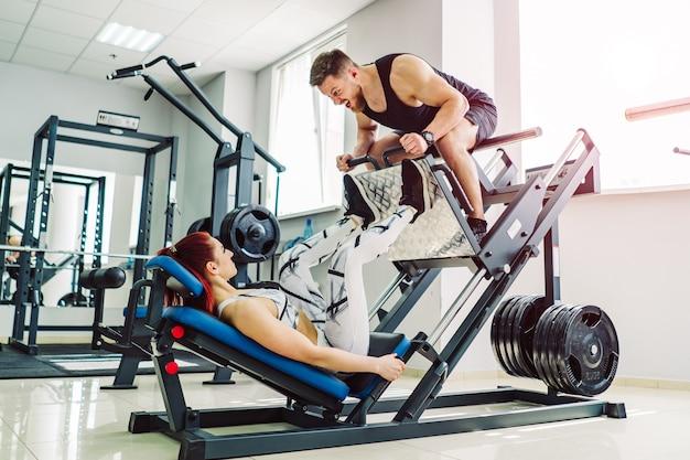 Jonge vrouw is bezig met een moderne simulator en een man zit erop in de sportschool. meisje traint met een trainer. vrouwelijke atleet doet oefeningen voor benen met trainingsmachine.
