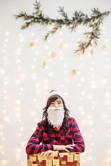 Jonge vrouw is een kerst-kerstman baard en hoed, in een rood geruit overhemd, licht wonderkaarsen