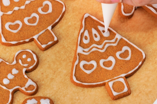 Jonge vrouw is het versieren van christmas gingerbread house koekjes koekje thuis met glazuur topping in suikerglazuur zak, close-up, lifestyle.