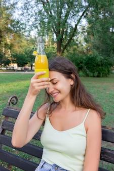 Jonge vrouw is moe van warm weer. het meisje houdt een koude fles sap dichtbij voorhoofd