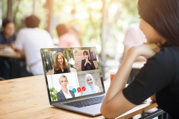 Jonge vrouw is op zoek naar haar computerscherm tijdens zakelijke bijeenkomst via video conferencing applicatie