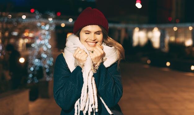 Jonge vrouw is vol geluk, buiten op straat wandelen, winterkleren dragen in de kersttijd